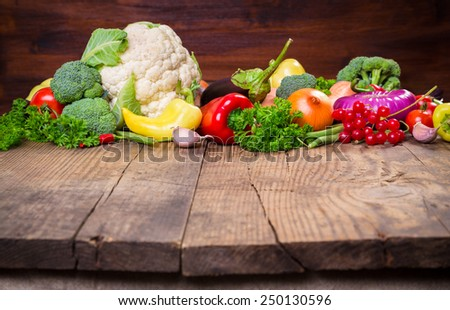 Plenty of colorful vegetables on wooden table with empty copy space - stock photo
