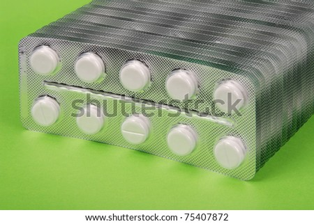 Plenty of white tablets in packing. Silver packs pills. Pills on green background