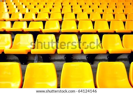 Plenty of yellow plastic seats at stadium - stock photo