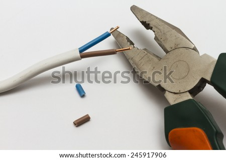 Pliers and electric cable stripped closeup. - stock photo
