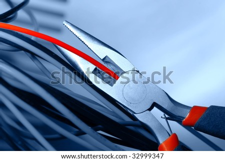 pliers cut the red cable - stock photo