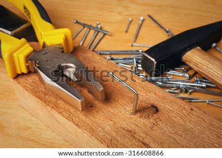 pliers  hammer and nail on a wooden board