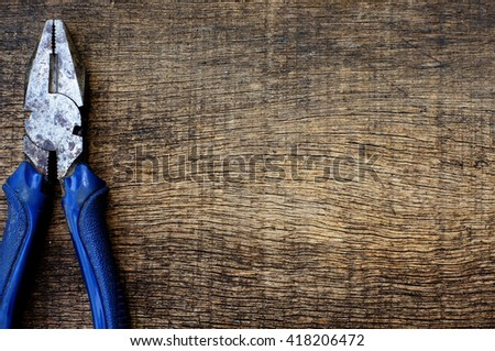 pliers on wood texture - stock photo
