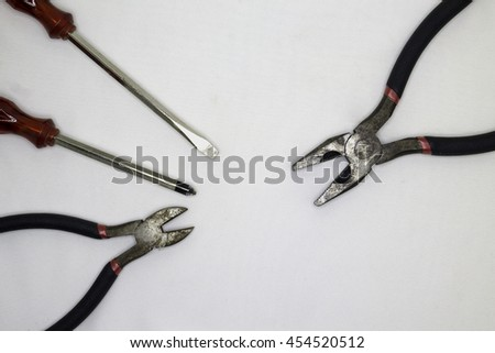 Pliers, screwdriver on a white background. - stock photo