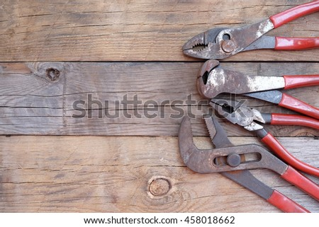 pliers set  red handle over a wood panel. Top view with copy space. - stock photo