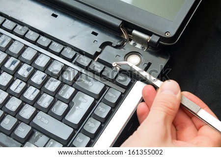 pliers to extract the screw from the computer - stock photo