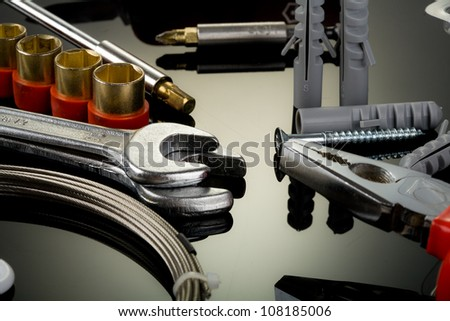 Pliers, wrenches and other tools on reflective surfaces - stock photo