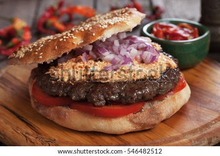 Pljeskavica, serbian style burger sandwich with urnebes topping