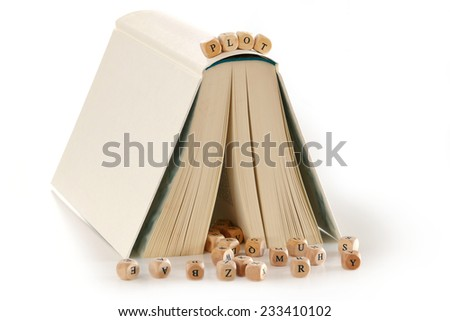 plot - message spelled out in wooden letters on top of a book that is set up like a house, several letters at the bottom, metaphor for story and creative writing, isolated on a white background - stock photo