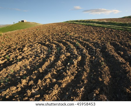 ploughed field and rural hut against cloudy sky - stock photo