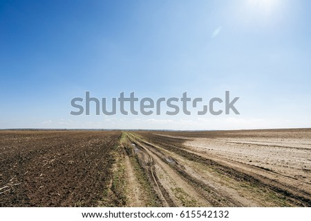 Ploughed field in spring prepared for sowing. Blue sky and road