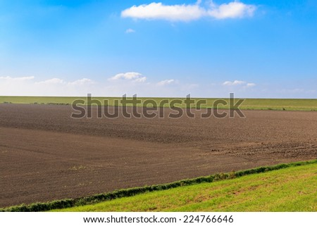 Ploughed field with protective dike against blue sky in East Frisia, Germany, near the Dutch border - stock photo