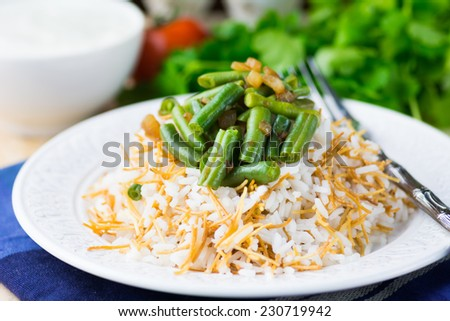Plov or pilaf with vermicelli, green beans and onions on white plate. Traditional middle eastern rice dish - stock photo