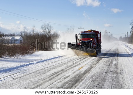 Plow clearing a rural road of snow outside Buffalo, New York.   - stock photo