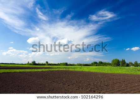 Plowed field and blue sky - stock photo