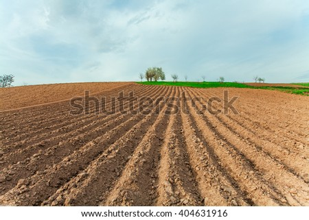 plowed field and cloudy sky in sunset - stock photo