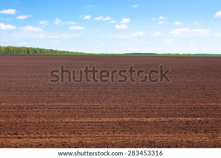 Plowed field in spring and clouds over it - stock photo