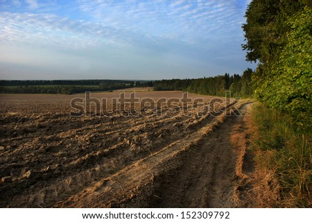 Plowed field in spring time with blue sky - stock photo