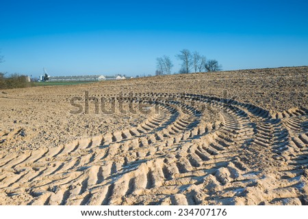 plowed field with tractor traces under blue sky
