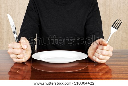 Plug and knife in hands with plate - stock photo