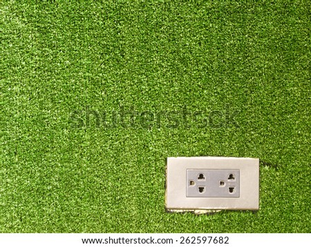 plug socket on artificial grass wall background - stock photo