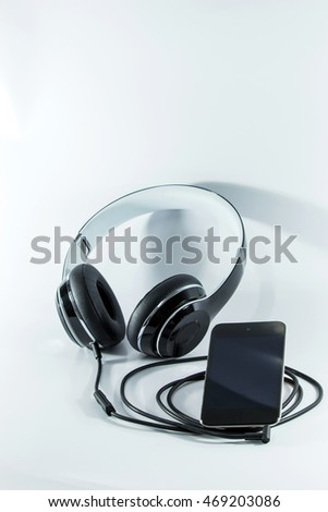 Plug the player device to the speakers and headphones on white background