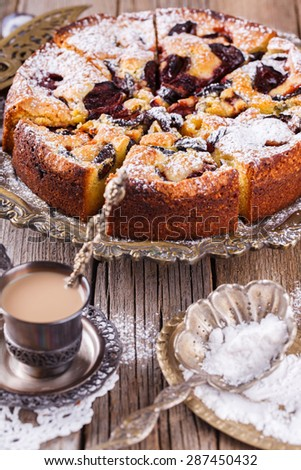 Plum cake with powdered sugar and a Cup of coffee.selective focus