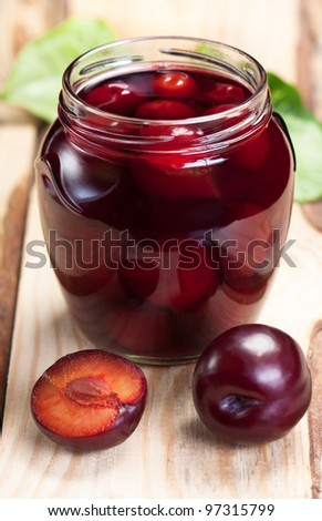 Plum compote glass jar on rough wooden table. - stock photo