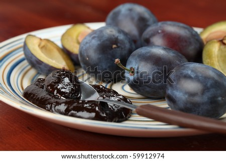 Plum jam and fresh plums on a plate. Shallow dof - stock photo