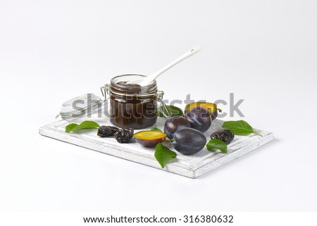plum jam, fresh and dried plums on wooden cutting board - stock photo
