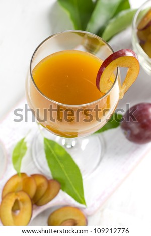 Plum juice and fresh fruits with leaves