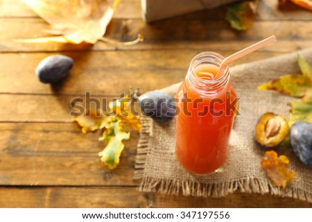 Plum Juice in a glass bottle with fresh fruits - stock photo