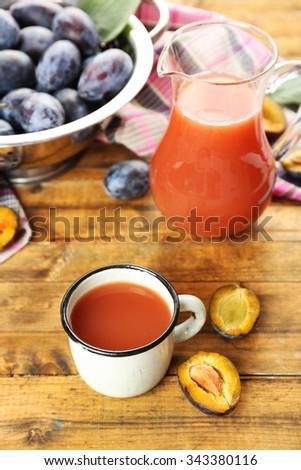 Plum Juice in jar and mug with fresh fruits - stock photo