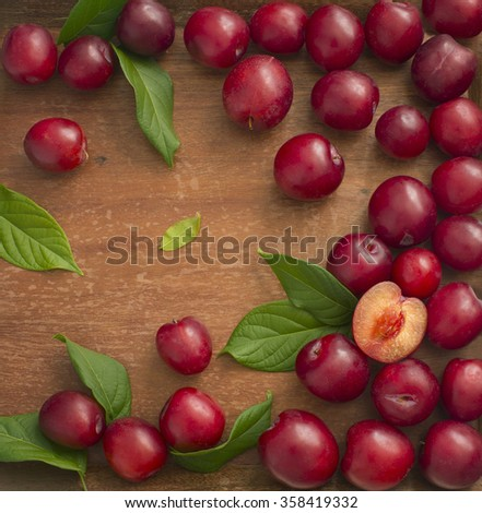Plum on wooden background. Text space image. Overhead view. - stock photo