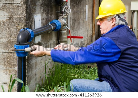 plumber at work in wastewater treatment plant - stock photo