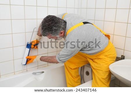 Plumber caulking bath tube with silicone glue using cartridge - stock photo