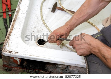 Plumber cleaning  drain in bathroom with cable - stock photo