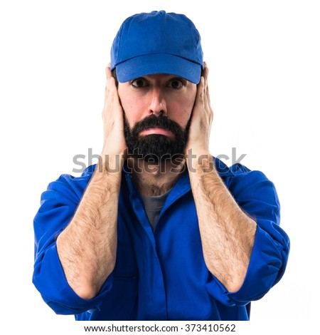 Plumber covering his ears - stock photo