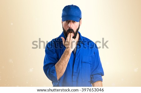 Plumber doing vomiting gesture over ocher background - stock photo