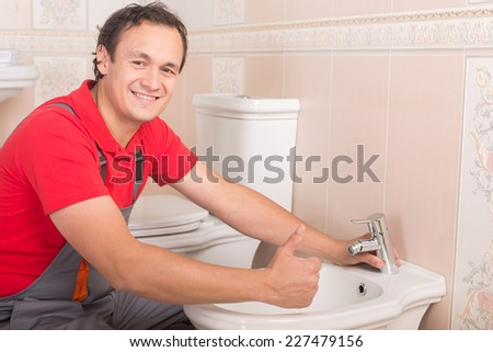 Plumber during his work in the toilet. - stock photo