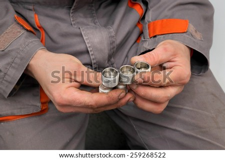 Plumber examine part of tube, pipe fitting, holding it in hands
