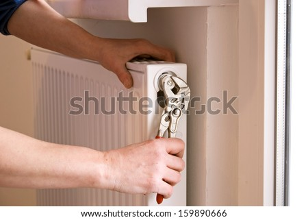plumber fixing a radiator with pliers on a construction site - stock photo