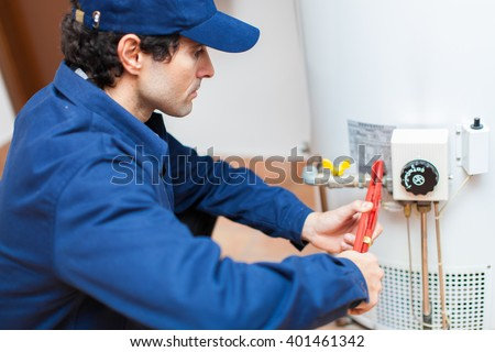 Plumber fixing an hot-water heater - stock photo