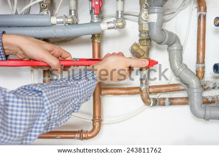 plumber fixing central heating system - stock photo