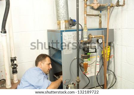 Plumber fixing gas furnace - stock photo