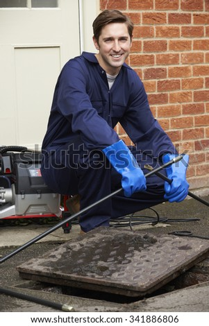 Plumber Fixing Problem With Drains - stock photo