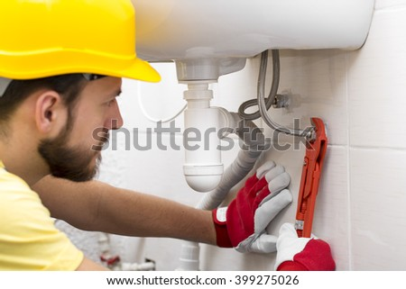 plumber fixing sink pipe with wrench in bathroom - stock photo