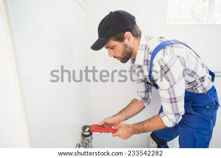 Plumber fixing tap with wrench in the bathroom - stock photo