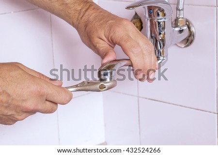 Plumber fixing the tap in the kitchen - stock photo