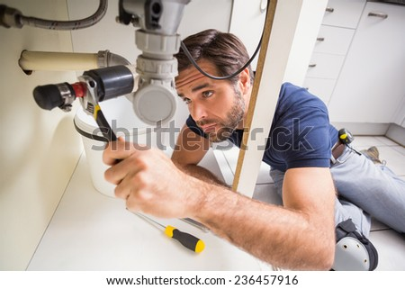 Plumber fixing under the sink in the kitchen - stock photo